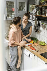 Affectionate couple in kitchen, preparing food - PESF01784