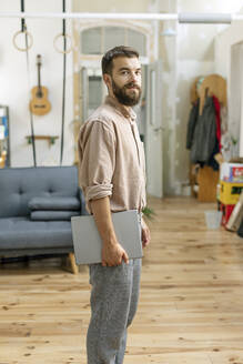 Confident young man standing at home, carrying digital tablet - PESF01790