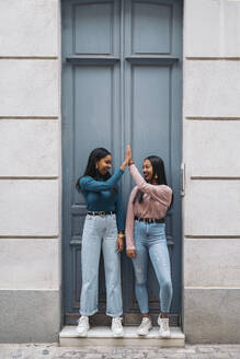 Two happy young women high fiving at a door in the city - MPPF00510
