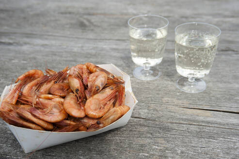 Cardboard box of shrimps and two plastic cups of white wine on wood - GISF00530