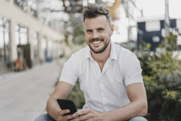 Young smiling man using smartphone and looking at camera - KNSF07599