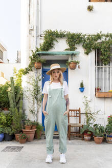 Portrait of young woman wearing dungarees and straw hat - AFVF05422