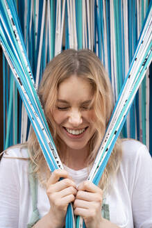 Portrait of laughing blond woman holding strings of door curtain - AFVF05425