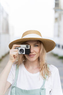Portrait of smiling young woman with camera - AFVF05428