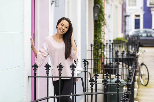 Portrait of smiling woman standing in front of residential house, Notting Hill, London, UK - WPEF02615