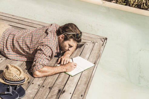 Man lying next to a pool writing in a notebook - SDAHF00161