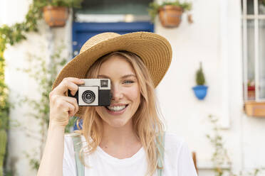 Portrait of happy young woman with camera - AFVF05436