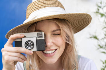 Portrait of smiling young woman wearing straw hat taking photo with camera - AFVF05439