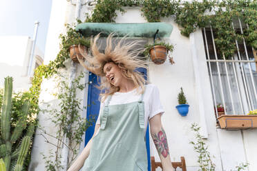 Happy young woman singing and tossing her hair in front of a house - AFVF05442