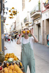 Laughing young woman on shopping street covering eyes with oranges - AFVF05451