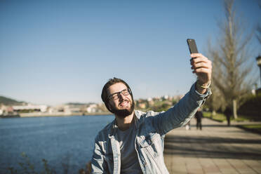 Young man taking smartphone selfies by the sea - RAEF02339