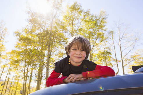 A smiling Six year old boy lying on the hood of a blue SUV in woodland. - MINF13663