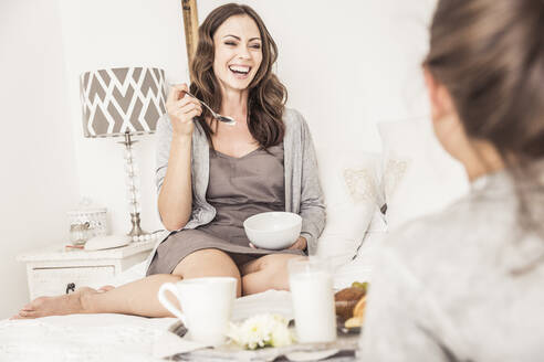 Portrait of laughing woman having breakfast with her daughter on bed - SDAHF00226