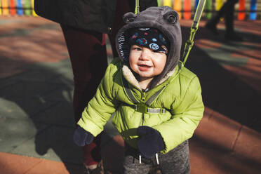 Portrait of happy baby boy at playground on sunny winter's day - BZF00531