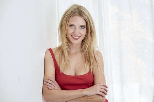 Portrait of smiling blond young woman wearing red top - PNEF02324