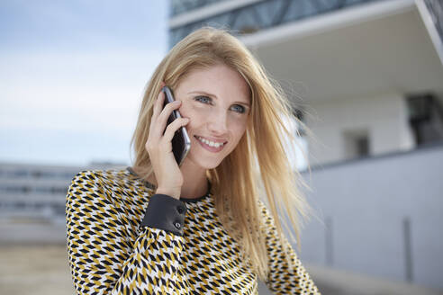 Portrait of smiling blond young woman on the phone - PNEF02330