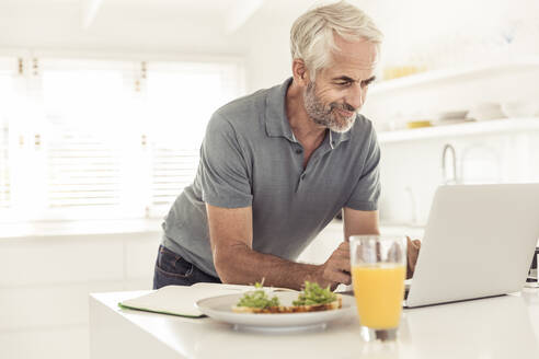 Mature man using laptop in kitchen at home - SDAHF00310