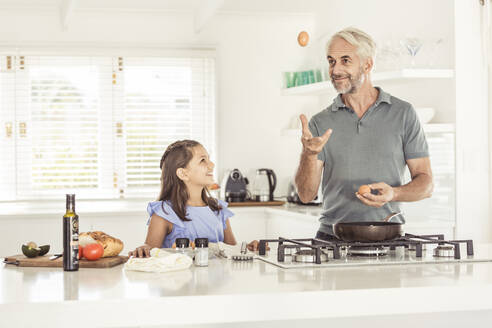 Father making fried egg for daughter at home - SDAHF00316