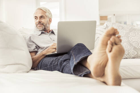 Mature man using laptop on couch at home - SDAHF00328