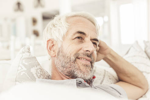 Portrait of mature man on couch in living room - SDAHF00331