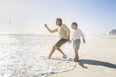 Father having fun with his son on the beach, throwing stones - SDAHF00383