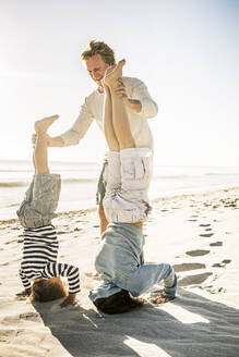 Father having fun with his son on the beach, practicing headstand - SDAHF00398