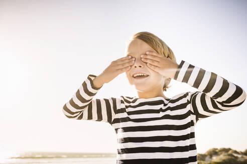 Happy boy on the beach covering his eyes - SDAHF00422