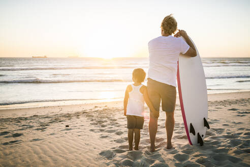 Rear view of father and son with surfboard standing on the beach at sunset - SDAHF00431