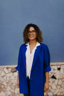 Portrait of smiling woman wearing glasses and blue blazer, blue wall in the background - TCEF00177