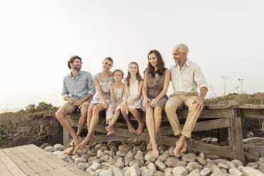 Large family enjoying the sunset sitting on a boardwalk - SDAHF00479