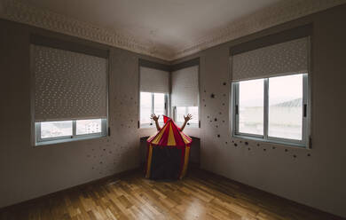 Person hiding behind toy tent in empty room - RAEF02351
