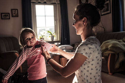 Mother dressing her little daughter in the living room - WFF00261