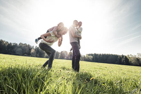 Happy family with two kids on a meadow in spring - WFF00273