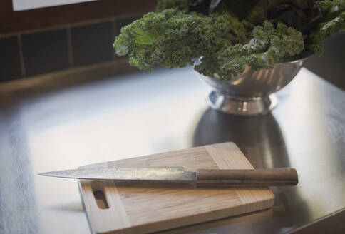 Still life knife on cutting board next to kale in colander - HOXF04910