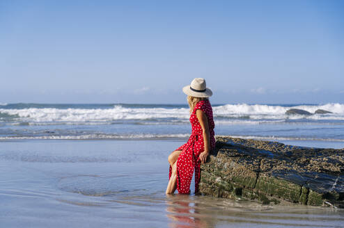 Blond woman wearing red dress and hat sittig on rock at the beach, Playa de Las Catedrales, Spain - DGOF00383