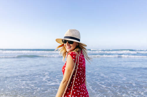 Blond woman wearing red dress and hat at the beach, turning and looking at camera - DGOF00407
