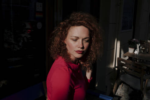 Portrait of red-haired woman at a cafe, looking sideways - OGF00116