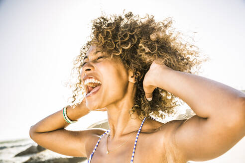 Portait of young woman screaming for joy on the beach - SDAHF00499