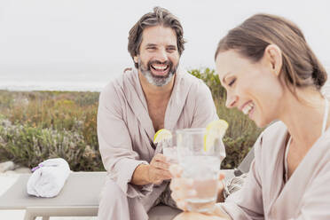 Happy relaxed couple with drinks on terrace - SDAHF00538