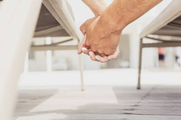 Close-up of couple holding hands on a terrace - SDAHF00541