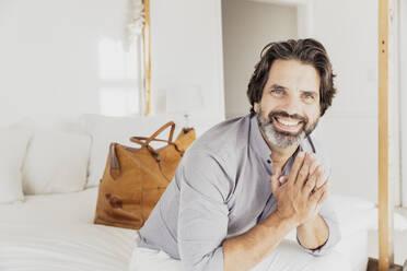 Portrait of happy bearded man sitting on bed - SDAHF00547
