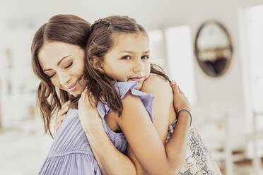 Affectionate mother hugging daughter at home - SDAHF00550