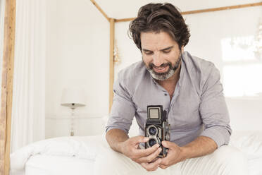 Bearded man sitting on bed with old-fashioned camera - SDAHF00559