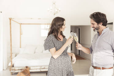 Happy couple clinking champagne glasses in bedroom - SDAHF00565