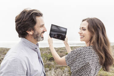 Happy man looking at wife holding tablet at the coast - SDAHF00574