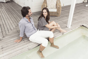 Happy couple relaxing at the poolside of a vacation home - SDAHF00577