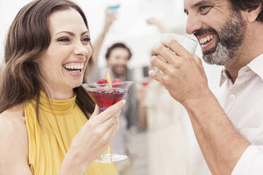 Happy couple and friends socializing on a cocktail party - SDAHF00586