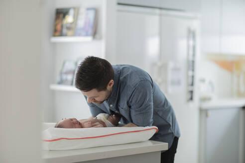 Man changing babys diaper - JOHF08914
