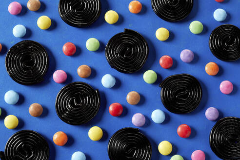 Spirals of liquorice interspersed with colorful sugar-coated chocolate candy on blue background - DREF00048