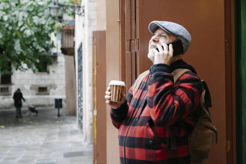 Senior man on the phone with coffee to go and backpack in the city, Barcelona, Spain - JCZF00011